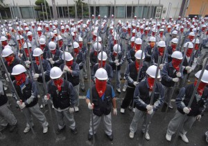 Workers of Ssangyong Motor hold iron bars at a strike rally at its main plant in Pyeongtaek